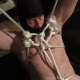 Mistress Troy creates a white rope harness for partial suspension of male slave in New York City
