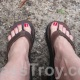 Dominatrix Mistress Troy slips her bare feet into a pair of flip-flops